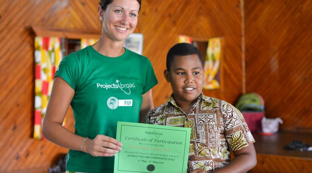 A young boy hands over a certificate to a Projects Abrpad volunteer for her volunteer work with children for teenagers in Fiji